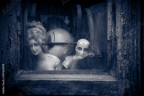 Papel de parede Creepy old vintage nostalgic dolls and figurines, looking out through cracked textured dirty window