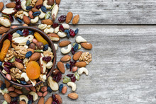 Nuts And Dried Fruits In A Bowl Over Rustic Wooden Table