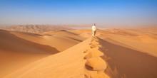 Arab Man In Kandoura Walking Over A Dune In The Arabian Desert