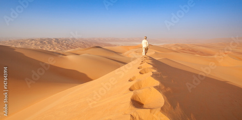 Poster Abou Dabi arab man in Kandoura walking over a Dune in the arabian Desert
