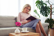 Nice female of age 30-40 concentrating on reading book