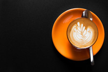 Hot Latte In Orange Cup With Floral Pattern In Foam On A Dark Background
