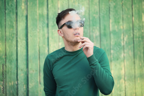Photo  Handsome young man smoking weed near wooden fence outdoors