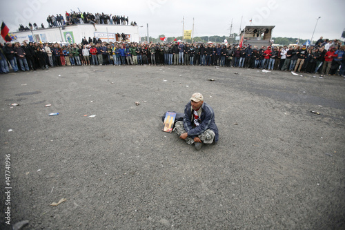 A Lone Protestor Sits In The Road In Front Of Others During Clashes