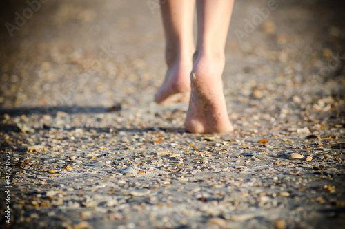 Photo Young child walking barefoot on sandy beach with shells