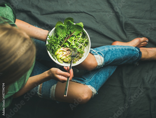 Fototapeta Green vegan breakfast meal in bowl with spinach, arugula, avocado, seeds and sprouts. Girl in jeans holding fork with knees and hands visible, top view. Clean eating, detox, vegetarian food concept obraz