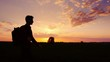 A teenager with a backpack over his shoulder goes towards the sunset in the field or in the countryside. Silhouette video, side view. Concept - new research, forward to the unknown, to leave home