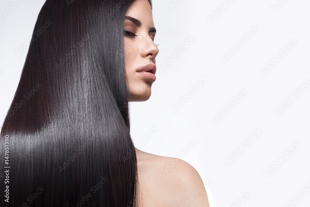 Fototapeta Beautiful brunette girl in move with a perfectly smooth hair, and classic make-up. Beauty face. Picture taken in the studio on a white background.