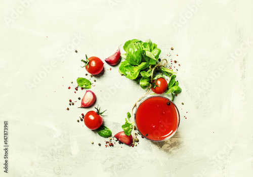 Food background, tomato juice, green basil, cherry tomatoes, garlic, salt, spices. Top view, flat lay
