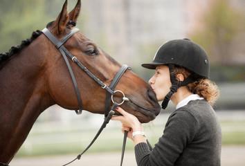 Atrakcyjna młoda kobieta całuje swojego konia