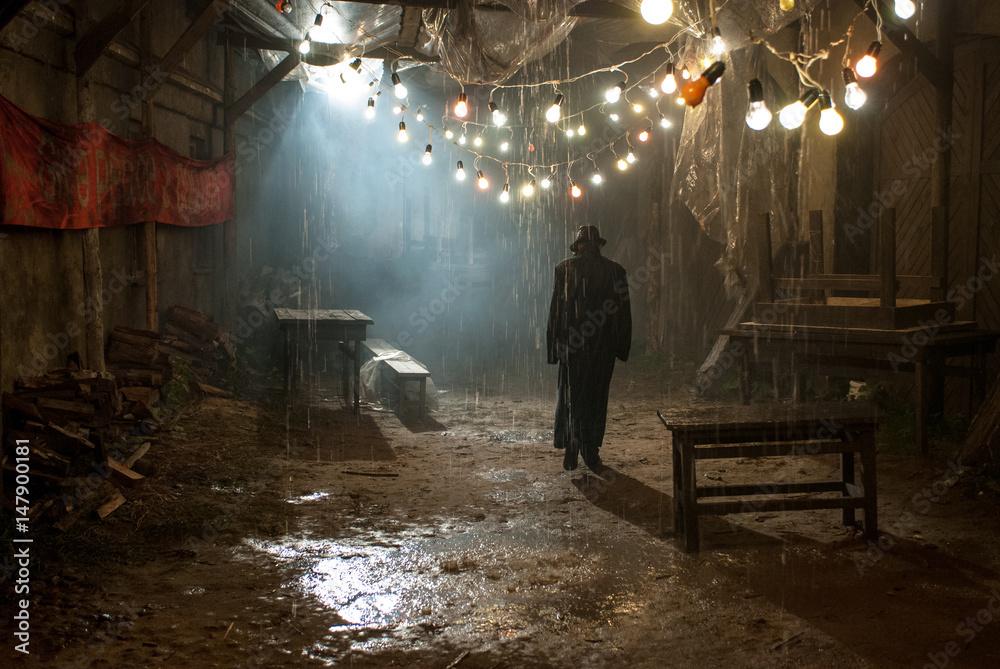 Fototapeta Man in black hat in the rain at dark overcast street