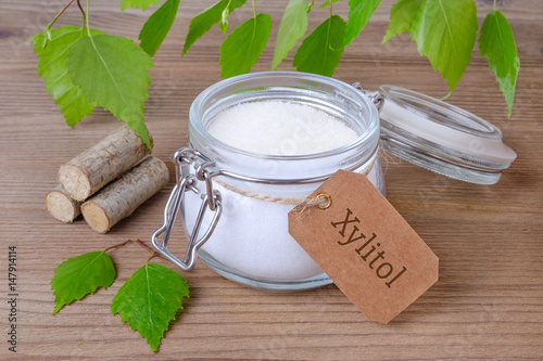 sugar substitute xylitol, a glass jar with birch sugar, liefs and wood