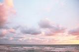 Lazurowe różowe chmury nad morzem o zachodzie słońca - 147914313