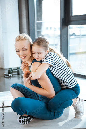 Fototapeta Cute girl embrace mother at fitness club obraz na płótnie
