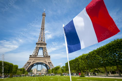 Poster Tour Eiffel French tricolor flag flying in blue sky in front of the Eiffel Tower in Paris, France
