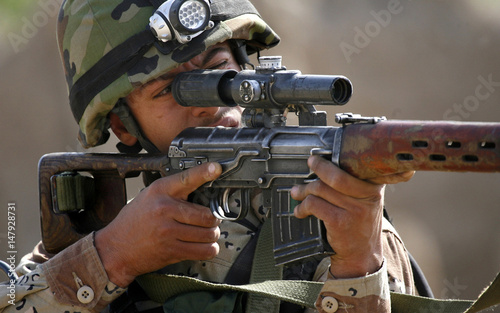 Iraqi army sniper scans the surrounding buildings during a