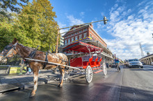 NEW ORLEANS, USA - FEBRUARY 2016: Red Horse Carriage Along Jackson Square. New Orleans Attracts 10 Million Tourists Annually