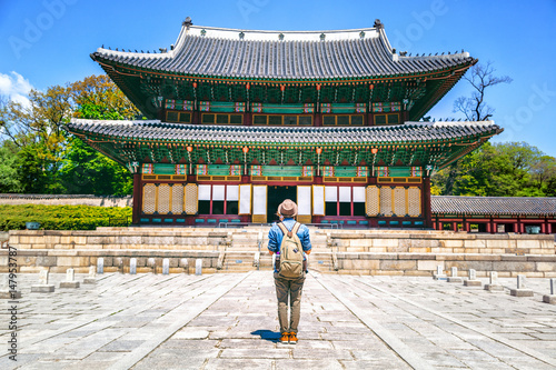 Stampe  girl tourist with a backpack standing in front of a beautiful historic pagoda