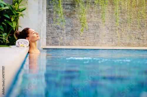 pielegnacja-urody-i-ciala-zmyslowa-mloda-kobieta-relaksuje-w-plenerowym-zdroju-plywackim-basenie