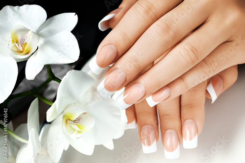 Staande foto Manicure Female hands with white nails on background of white flowers.