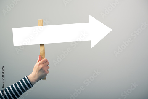 Photo  Woman holding guiding direction arrow sign