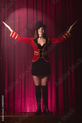Beautiful woman trainer in a circus suit