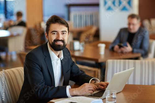 Fototapety, obrazy: Smiling middle-aged financial manager with bushy beard looking at camera while sitting in lovely cafe and making corrections in annual accounting reports, waist-up portrait