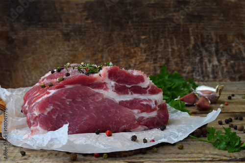 Foto op Aluminium Vlees raw piece meat of pork and spices marinade on wooden background. For steak, roasting, stewing. Space for text