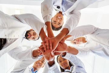 Multikulturelles Ärzte Team stapelt Hände