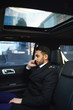 Side view portrait of handsome Middle-Eastern businessman speaking by phone on backseat inside expensive car
