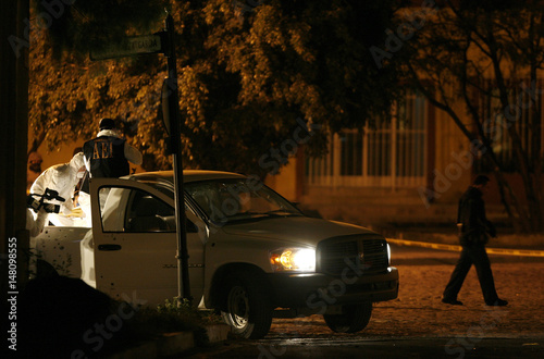 Forensic personnel remove a body from the bed of a truck at