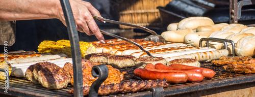 Fototapeta Grillfest: Frau bereitet Bratwürste und Steaks zu obraz