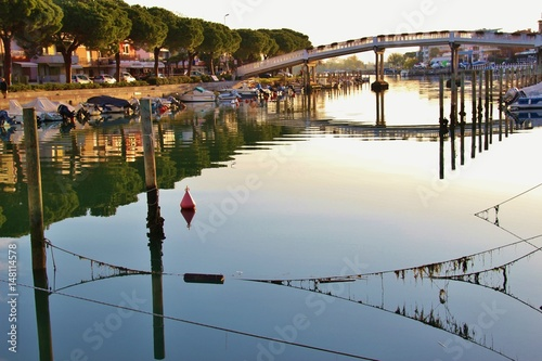 City on the water Canal and boats in Grado in bright morning light. North-Eastern Italy, Europe.