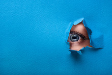 A Female Eye Looks Through A Hole In A Paper Blue Background.
