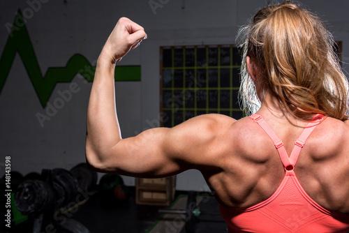 Woman doing a bicep flex in gym Canvas Print