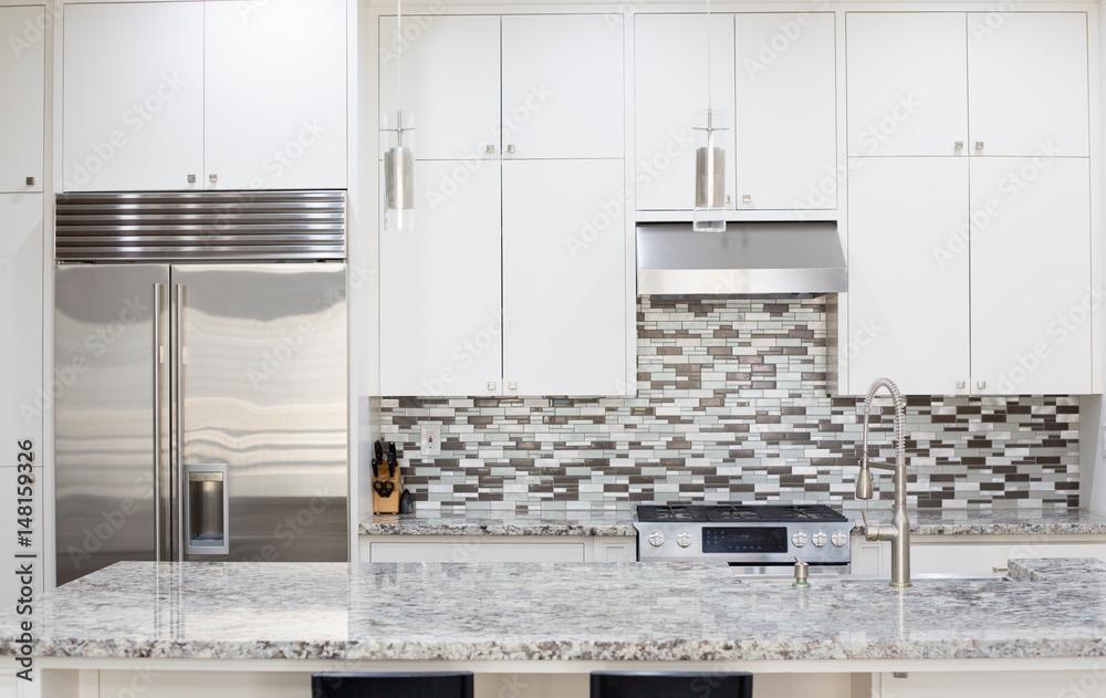 Fototapeta Snapshot of interior modern kitchen with granite countertop island and smart refrigerator