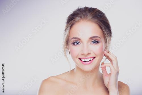 Plakat Młoda kobieta dotyka jej twarz odizolowywającą na białym tle
