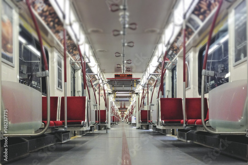 Interior of empty subway car with bright red seats