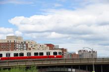 Red Train Crossing Long Field Bridge Above Charles River In Boston