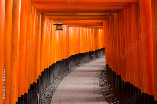 Torii gates in Fushimi Inari-taisha outside Kyoto, Japan. Orange, natural glow in morning light. Lantern hanging to the top left