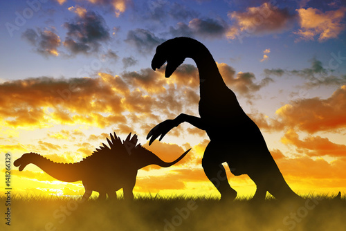 Foto op Aluminium Draken Silhouette of dinosaurs in the sunset.