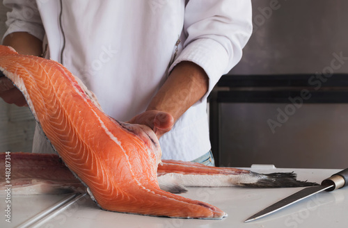 Photographie Chef's hand holding fresh piece of salmon