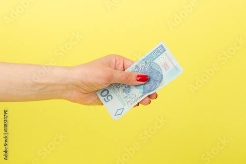 Fotomural  Polish zloty in the woman's hand, yellow background