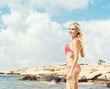 Beautiful, attractive woman in pink bikini. Young and sporty girl posing on a beach at summer. Holiday, resort, tourism, concept.