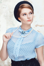 Elegant Young Woman Wearing Blue Blouse, Pearl Necklace And Beret Posing On Grunge Background