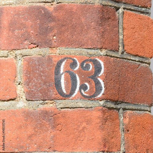 Fotografia  House number 63 painted sign