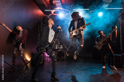 Valokuva Young multiethnic rock and roll band performing hard rock music on stage
