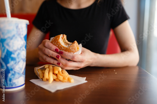 Obraz na plátně Young girl holding in female hands fast food burger, american unhealthy meal on
