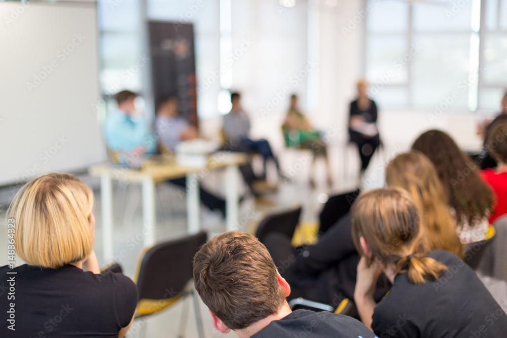 Fototapeta Round table discussion at business and entrepreneurship symposium. Audience in conference hall. Lens focus on unrecognized participant in rear of audience.
