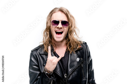 Valokuvatapetti portrait of handsome rocker in black leather jacket and sunglasses showing rock
